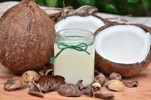 kokosová olej ve sklenici a kokosový ořech